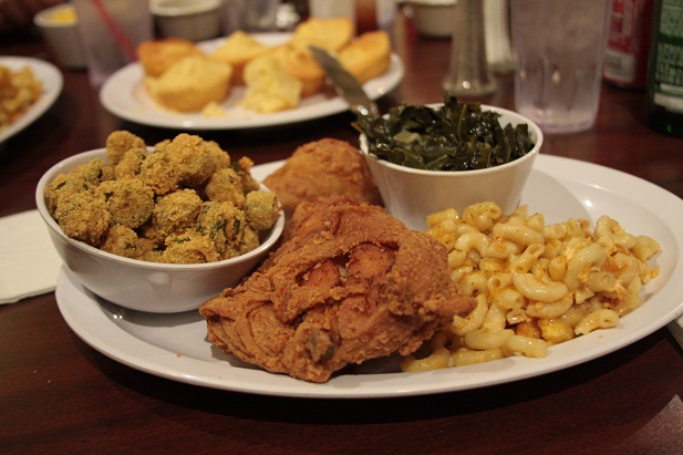 Fried chicken fried okra collard greens and mac and cheese together on a plate